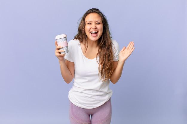 Młoda ładna kobieta czuje się szczęśliwa i zdumiona czymś niewiarygodnym i trzyma kawę