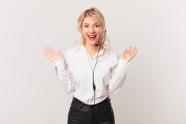 Młoda ładna kobieta czuje się szczęśliwa i zdumiona czymś niewiarygodnym. koncepcja telemarketingu