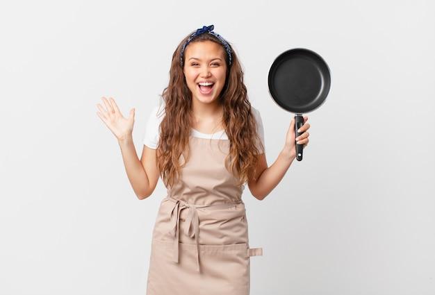 Młoda ładna kobieta czuje się szczęśliwa i zdumiona czymś niewiarygodnym pomysłem szefa kuchni i trzyma patelnię