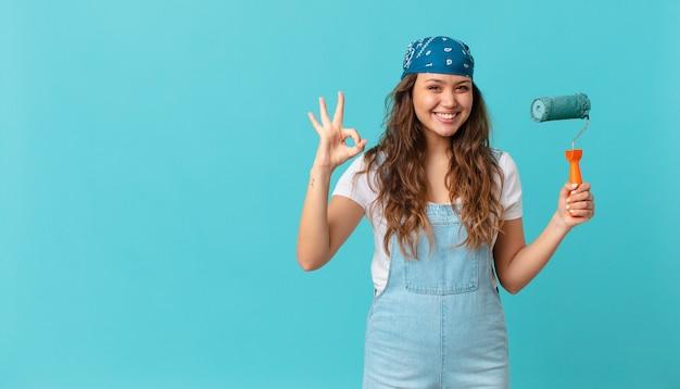 Młoda ładna kobieta czuje się szczęśliwa, okazując aprobatę dobrym gestem i malując ścianę
