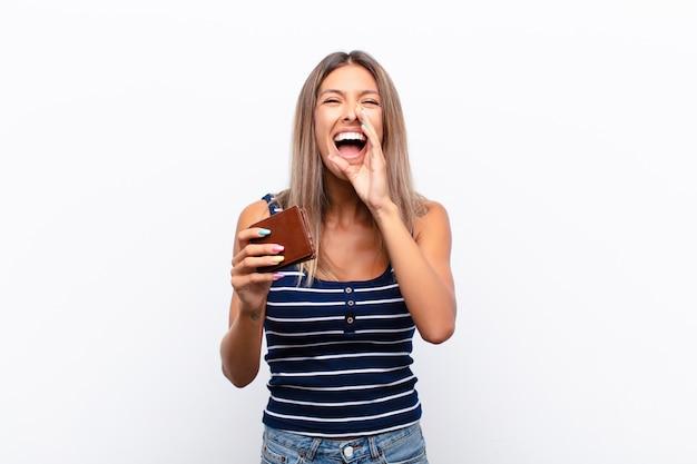 Młoda ładna kobieta czuje się szczęśliwa, podekscytowana i pozytywna, głośno krzyczy rękami przy ustach, wołając skórzanym portfelem