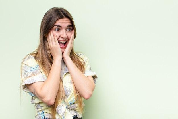 Młoda ładna kobieta czuje się szczęśliwa, podekscytowana i zaskoczona, patrząc z boku obiema rękami na twarzy