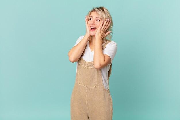 Młoda ładna kobieta czuje się szczęśliwa, podekscytowana i zaskoczona