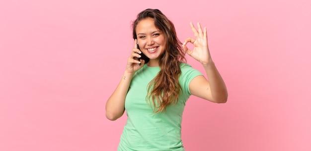 Młoda ładna kobieta czuje się szczęśliwa, pokazując aprobatę dobrym gestem i trzymająca smartfona