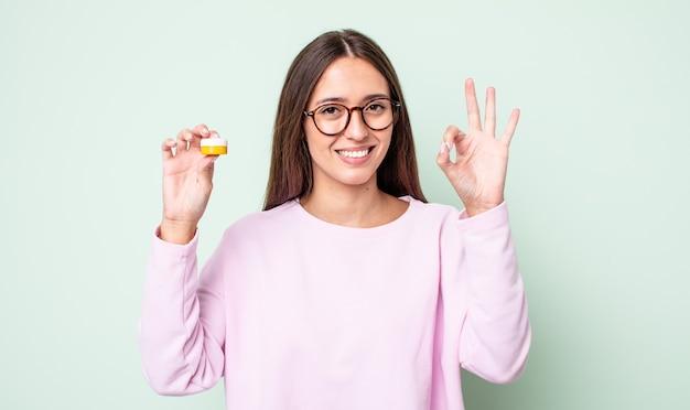 Młoda ładna kobieta czuje się szczęśliwa, pokazując aprobatę w porządku gestem. koncepcja soczewek kontaktowych