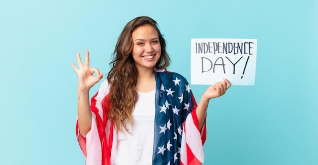 Młoda ładna kobieta czuje się szczęśliwa, pokazując aprobatę z koncepcją dnia niepodległości w porządku gest