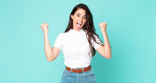 Młoda ładna kobieta czuje się szczęśliwa, pozytywna i odnosi sukcesy, świętuje zwycięstwo, osiągnięcia lub szczęście