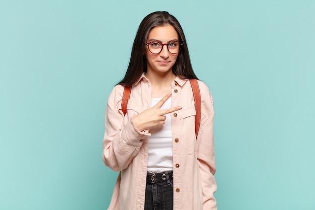 Młoda ładna kobieta czuje się szczęśliwa, pozytywna i odnosi sukcesy, z ręką tworzącą kształt litery v nad klatką piersiową, pokazując zwycięstwo lub pokój