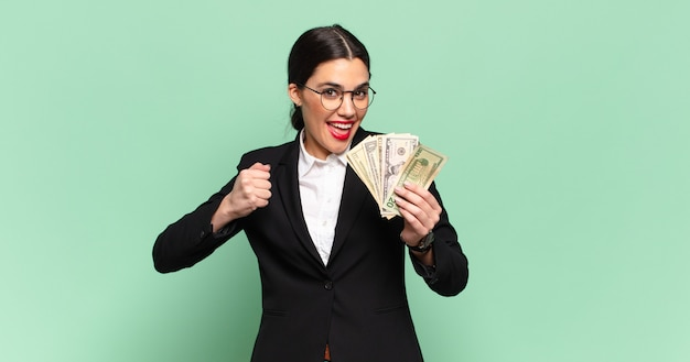 Młoda ładna kobieta czuje się szczęśliwa, pozytywna i odnosi sukcesy, zmotywowana, gdy mierzy się z wyzwaniem lub świętuje dobre wyniki. koncepcja biznesu i banknotów