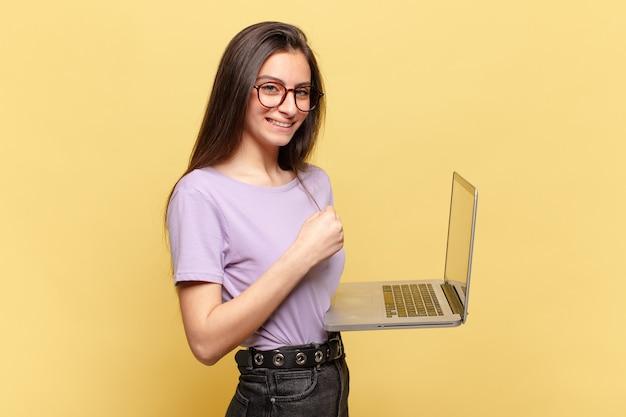 Młoda ładna kobieta czuje się szczęśliwa, pozytywna i odnosi sukcesy, zmotywowana, gdy mierzy się z wyzwaniem lub świętuje dobre wyniki. koncepcja laptopa