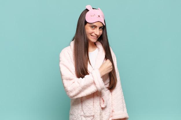 Młoda ładna kobieta czuje się szczęśliwa, pozytywna i odnosi sukcesy, zmotywowana, gdy staje przed wyzwaniem lub świętuje dobre wyniki