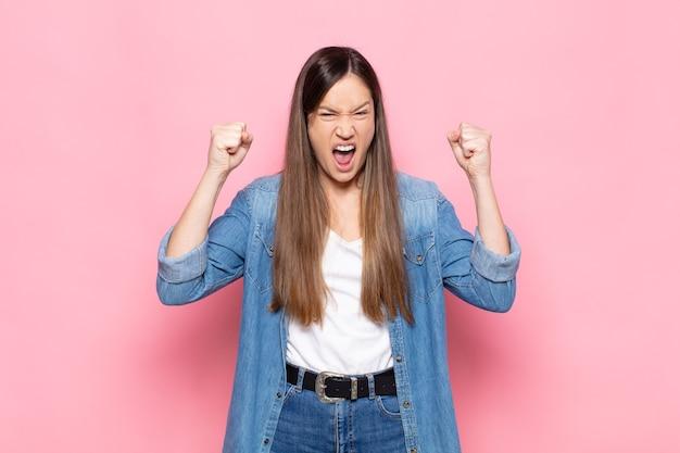 Młoda ładna kobieta czuje się szczęśliwa, pozytywna i odnosząca sukcesy, świętuje zwycięstwo, osiągnięcia lub powodzenia