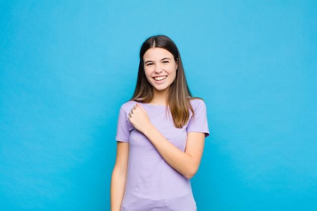 Młoda ładna kobieta czuje się szczęśliwa, pozytywna i odnosząca sukcesy, zmotywowana, gdy stoi przed wyzwaniem lub świętuje dobre wyniki na niebieskiej ścianie