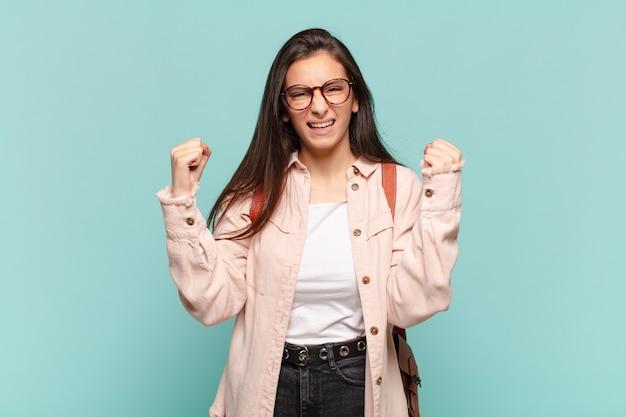 Młoda ładna kobieta czuje się szczęśliwa, pozytywna i odnosząca sukcesy
