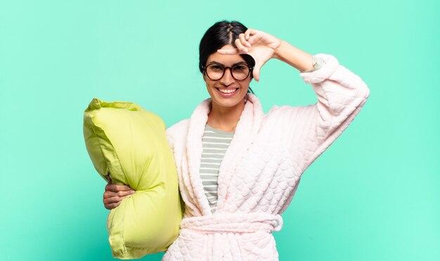 Młoda ładna kobieta czuje się szczęśliwa, przyjazna i pozytywna, uśmiechając się i robiąc portret lub ramkę na zdjęcia rękami. koncepcja piżamy