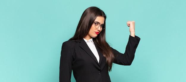 Młoda ładna kobieta czuje się szczęśliwa, usatysfakcjonowana i potężna, wygina się i ma umięśnione bicepsy, wygląda na silną po siłowni