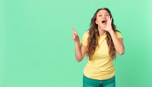 Młoda ładna kobieta czuje się szczęśliwa, wydając wielki okrzyk z rękami przy ustach i wskazując na miejsce na kopię
