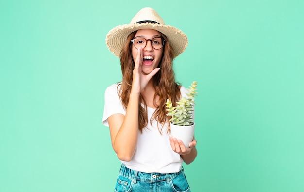 Młoda ładna kobieta czuje się szczęśliwa, wydając wielki okrzyk z rękami przy ustach w słomkowym kapeluszu i trzymając kaktus