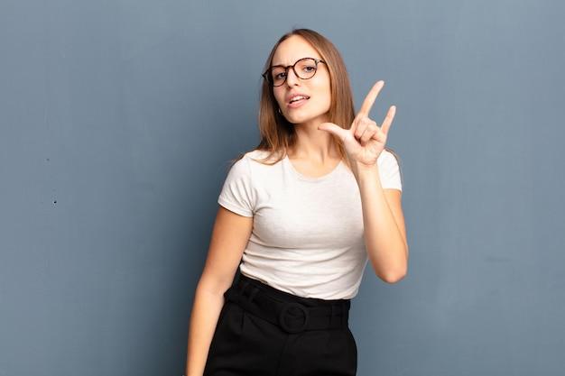 Młoda ładna kobieta czuje się szczęśliwa, zabawna, pewna siebie, pozytywna i zbuntowana, czyniąc znak rocka lub metalu ciężkiego ręką na szarym tle