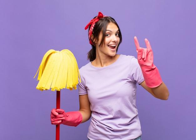 Młoda ładna kobieta czuje się szczęśliwa, zabawna, pewna siebie, pozytywna i zbuntowana, robi ręką rockowy lub heavy metalowy znak