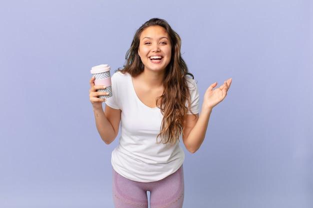 Młoda ładna kobieta czuje się szczęśliwa, zaskoczona, gdy zdaje sobie sprawę z rozwiązania lub pomysłu i trzyma kawę