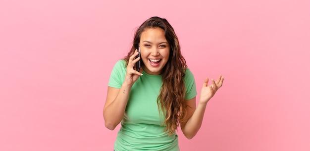 Młoda ładna kobieta czuje się szczęśliwa, zaskoczona, gdy zdaje sobie sprawę z rozwiązania lub pomysłu i trzyma smartfona