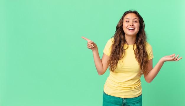Młoda ładna kobieta czuje się szczęśliwa, zaskoczona, gdy zdaje sobie sprawę z rozwiązania lub pomysłu i wskazuje na miejsce na kopię