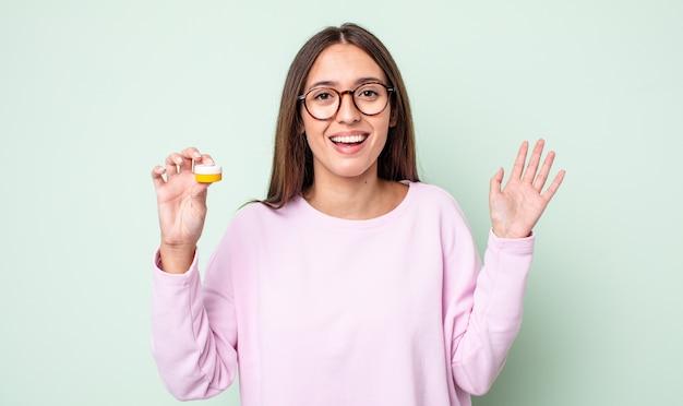 Młoda ładna kobieta czuje się szczęśliwa, zaskoczona, gdy zdaje sobie sprawę z rozwiązania lub pomysłu. koncepcja soczewek kontaktowych