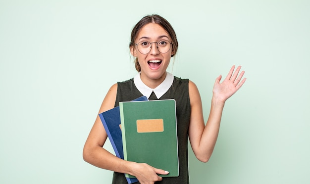 Młoda ładna kobieta czuje się szczęśliwa, zaskoczona, gdy zdaje sobie sprawę z rozwiązania lub pomysłu. koncepcja uniwersytecka