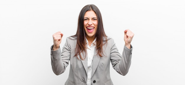 Młoda ładna kobieta czuje się szczęśliwa, zaskoczona i dumna, krzyczy i świętuje sukces z wielkim uśmiechem na białym tle białej ścianie
