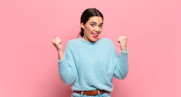 Młoda ładna kobieta czuje się szczęśliwa, zaskoczona i dumna, krzyczy i świętuje sukces z wielkim uśmiechem