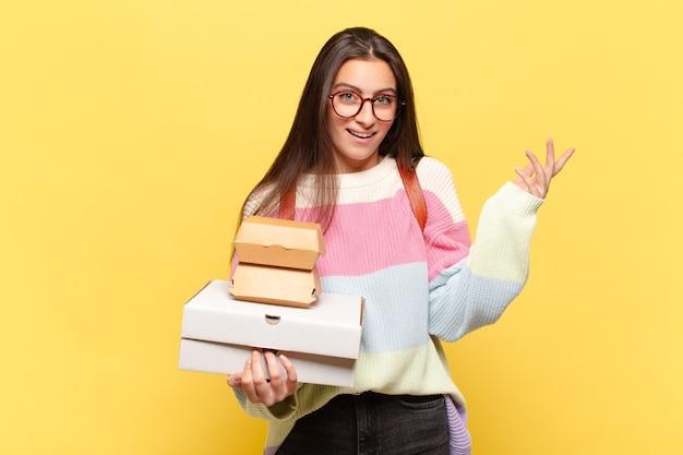 Młoda ładna kobieta czuje się szczęśliwa, zaskoczona i pogodna, uśmiechnięta z pozytywnym nastawieniem, realizująca rozwiązanie lub pomysł. weź koncepcję fast foodów aeay