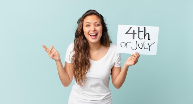 Młoda ładna kobieta czuje się szczęśliwa, zaskoczona, realizując koncepcję dnia niepodległości rozwiązania lub pomysłu