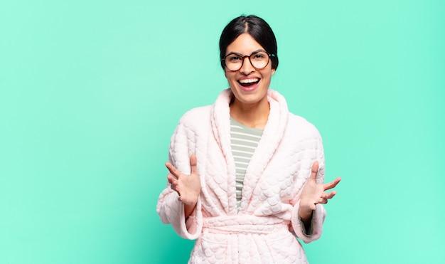 Młoda ładna kobieta czuje się szczęśliwa, zdziwiona, szczęśliwa i zdziwiona, jakby mówiła poważnie, omg? nie do wiary. koncepcja piżamy