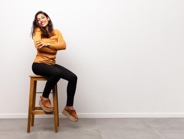 Młoda ładna kobieta czuje się szczęśliwa, zdziwiona, szczęśliwa i zdziwiona, mówiąc poważnie o omg? niewiarygodne siedzenie w pokoju