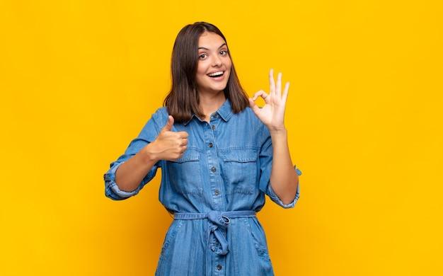 Młoda ładna kobieta czuje się szczęśliwa, zdziwiona, usatysfakcjonowana i zaskoczona, pokazując gesty w porządku i kciuki do góry, uśmiechając się
