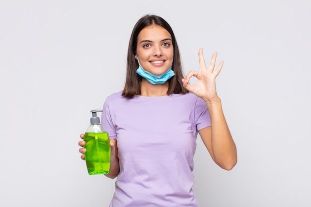 Młoda ładna kobieta czuje się szczęśliwa, zrelaksowana i usatysfakcjonowana, okazując aprobatę w porządku gestem