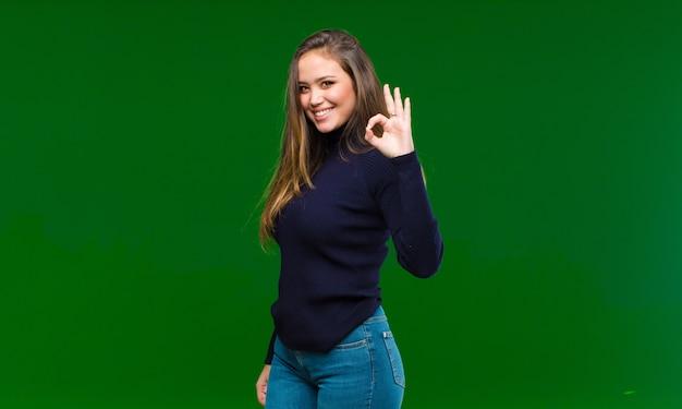 Młoda ładna kobieta czuje się szczęśliwa, zrelaksowana i usatysfakcjonowana, pokazując aprobatę w porządku gestem, uśmiechając się do zielonej ściany
