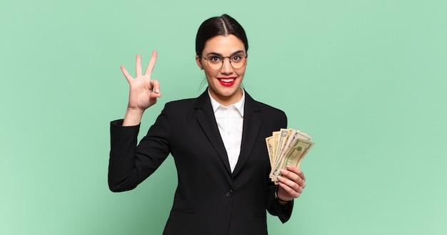 Młoda ładna kobieta czuje się szczęśliwa, zrelaksowana i zadowolona, okazując aprobatę dobrym gestem, uśmiechając się. koncepcja biznesu i banknotów