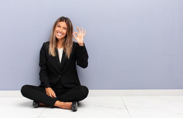 Młoda ładna kobieta czuje się szczęśliwa, zrelaksowana i zadowolona, pokazując zgodę z dobrym gestem, uśmiechając się