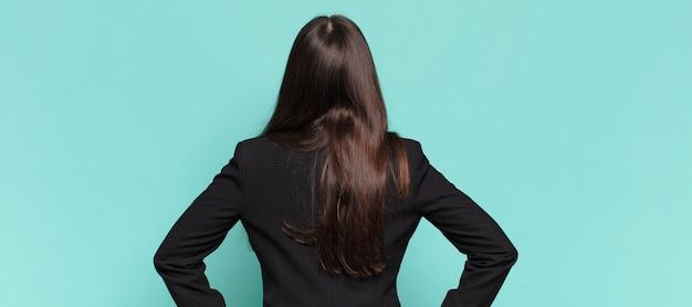 Młoda ładna kobieta czuje się zagubiona lub pełna lub ma wątpliwości i pytania, zastanawiając się, z rękami na biodrach, widok z tyłu. pomysł na biznes