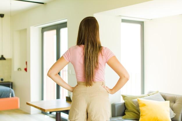 Młoda ładna kobieta czuje się zagubiona lub pełna lub ma wątpliwości i pytania, zastanawiając się, z rękami na biodrach, widok z tyłu
