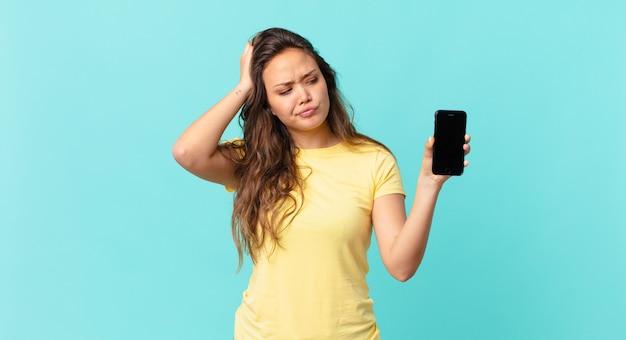 Młoda ładna kobieta czuje się zakłopotana i zdezorientowana, drapiąc się po głowie i trzymająca smartfona