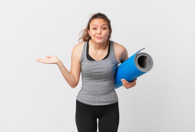 Młoda ładna kobieta czuje się zakłopotana i zdezorientowana, wątpi i trzyma matę do jogi