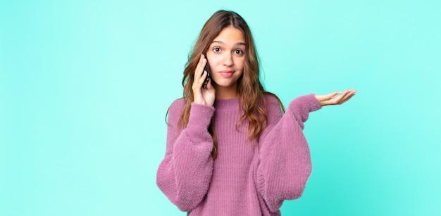 Młoda ładna kobieta czuje się zakłopotana i zdezorientowana, wątpi i używa smartfona