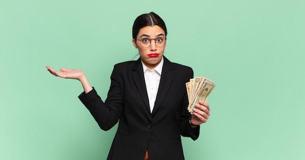 Młoda ładna kobieta czuje się zakłopotana i zdezorientowana, wątpi, waży lub wybiera różne opcje z zabawnym wyrazem twarzy. koncepcja biznesu i banknotów