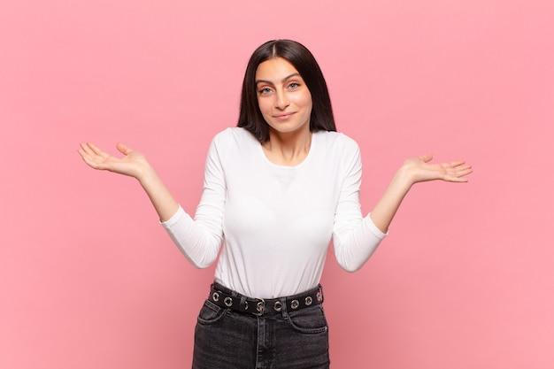 Młoda ładna kobieta czuje się zakłopotana i zdezorientowana, wątpi, waży lub wybiera różne opcje ze śmiesznym wyrazem twarzy