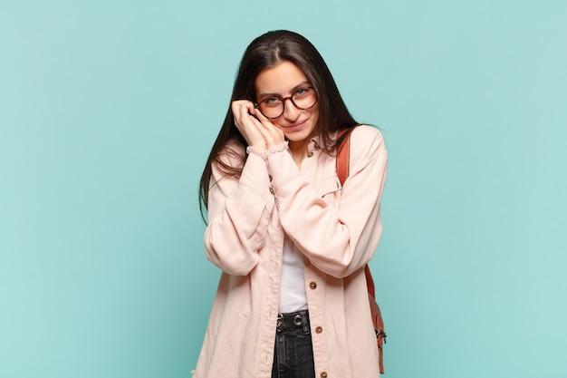 Młoda ładna kobieta czuje się zakochana i wygląda uroczo, uroczo i szczęśliwie, uśmiechając się romantycznie z rękami obok twarzy. koncepcja studenta