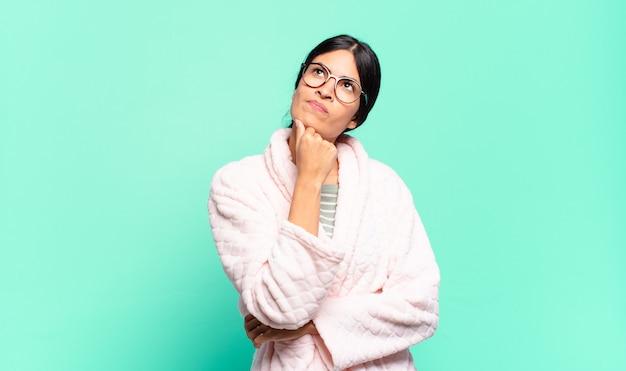 Młoda ładna kobieta czuje się zamyślona, zastanawia się lub ma pomysły, marzy i patrzy w górę, aby skopiować przestrzeń. koncepcja piżamy