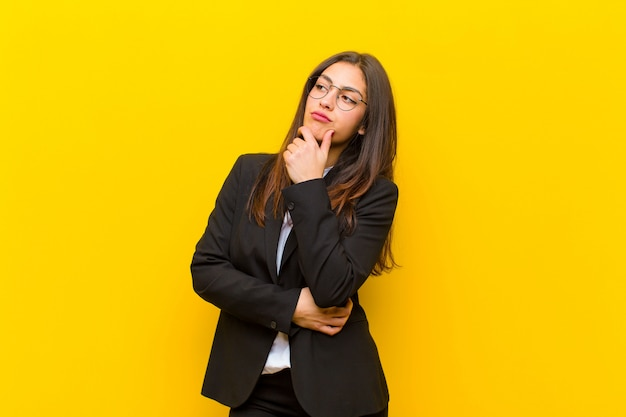 Młoda ładna kobieta czuje się zamyślona, zastanawia się lub wyobraża sobie pomysły, marzy i szuka do copyspace na pomarańczowej ścianie